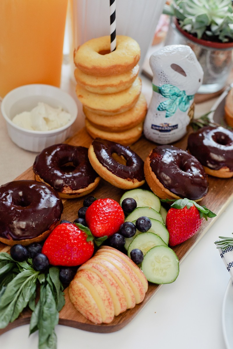 Easter Brunch Ideas: 5 Surprising Ways to Make Your Holiday Easier |Easter Brunch Ideas by popular Florida lifestyle blog, Fresh Mommy Blog: image of a wooden cutting board filled with cucumber slices, strawberries, blueberries, glazed donuts, chocolate frosted donuts, and a chocolate bunny.