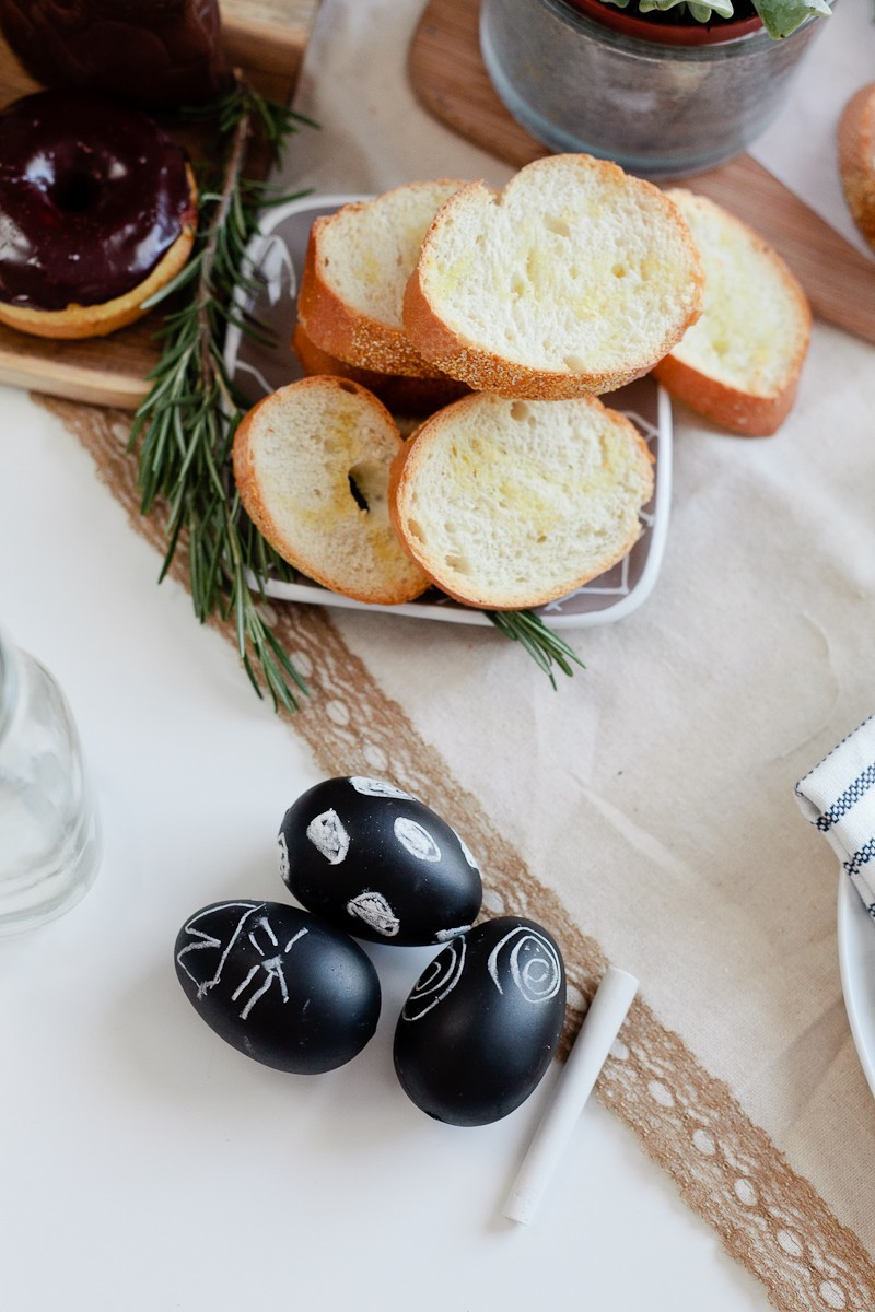 Easter brunch ideas |Easter Brunch Ideas by popular Florida lifestyle blog, Fresh Mommy Blog: image of sliced bread in a square white ceramic dish an some black chalkboard eggs with designs drawn on them in white chalk.