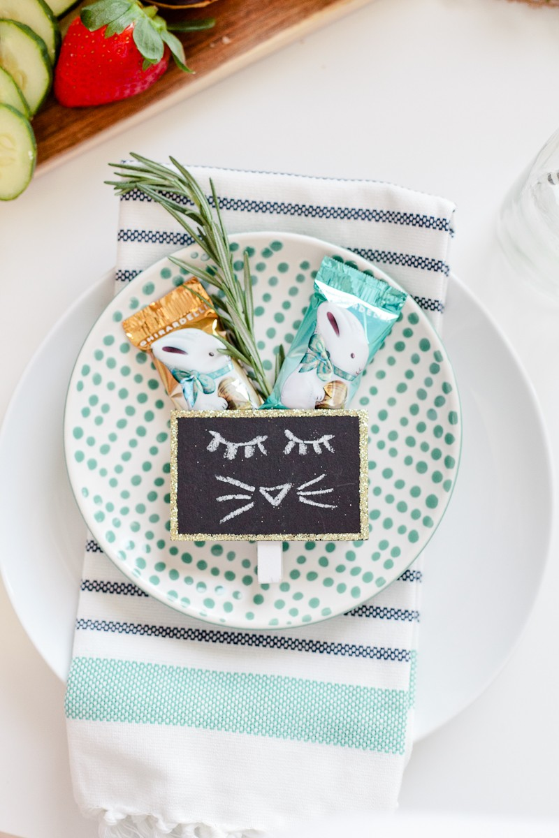 Easter Brunch Ideas: 5 Surprising Ways to Make Your Holiday Easier |Easter Brunch Ideas by popular Florida lifestyle blog, Fresh Mommy Blog: image of a white ceramic plate with dots  containing two chocolate bunnies, a fresh rosemary sprig, ad chalkboard place setting with a bunny face drawn on it ad resting on a blue and white stripe cloth napkin that's resting on top of a larger white ceramic plate.