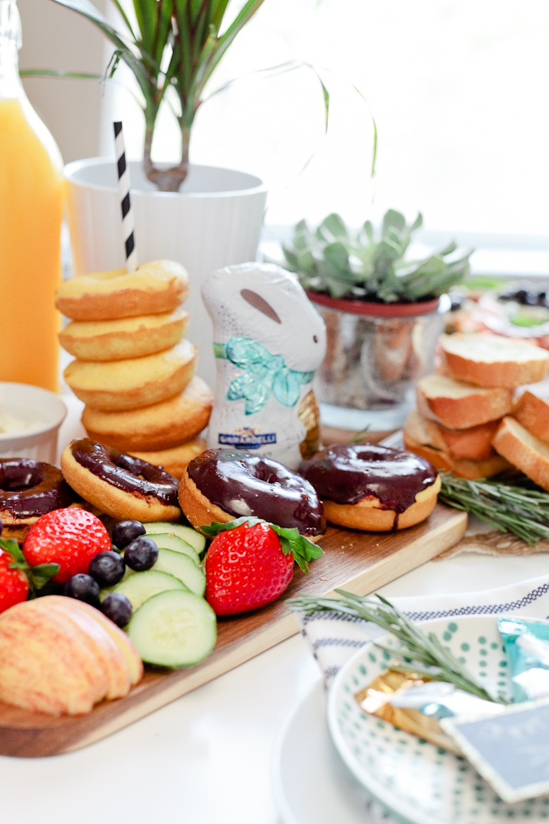 easter brunch ideas | Easter Brunch Ideas by popular Florida lifestyle blog, Fresh Mommy Blog: image of a wooden cutting board filled with cucumber slices, strawberries, blueberries, glazed donuts, chocolate frosted donuts, and a chocolate bunny.