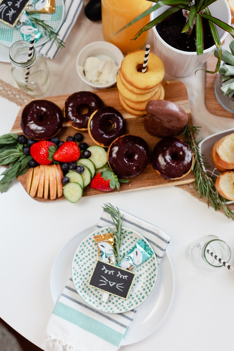easter brunch ideas |Easter Brunch Ideas by popular Florida lifestyle blog, Fresh Mommy Blog: image of a wooden cutting board filled with cucumber slices, strawberries, blueberries, glazed donuts, chocolate frosted donuts, and a chocolate bunny.