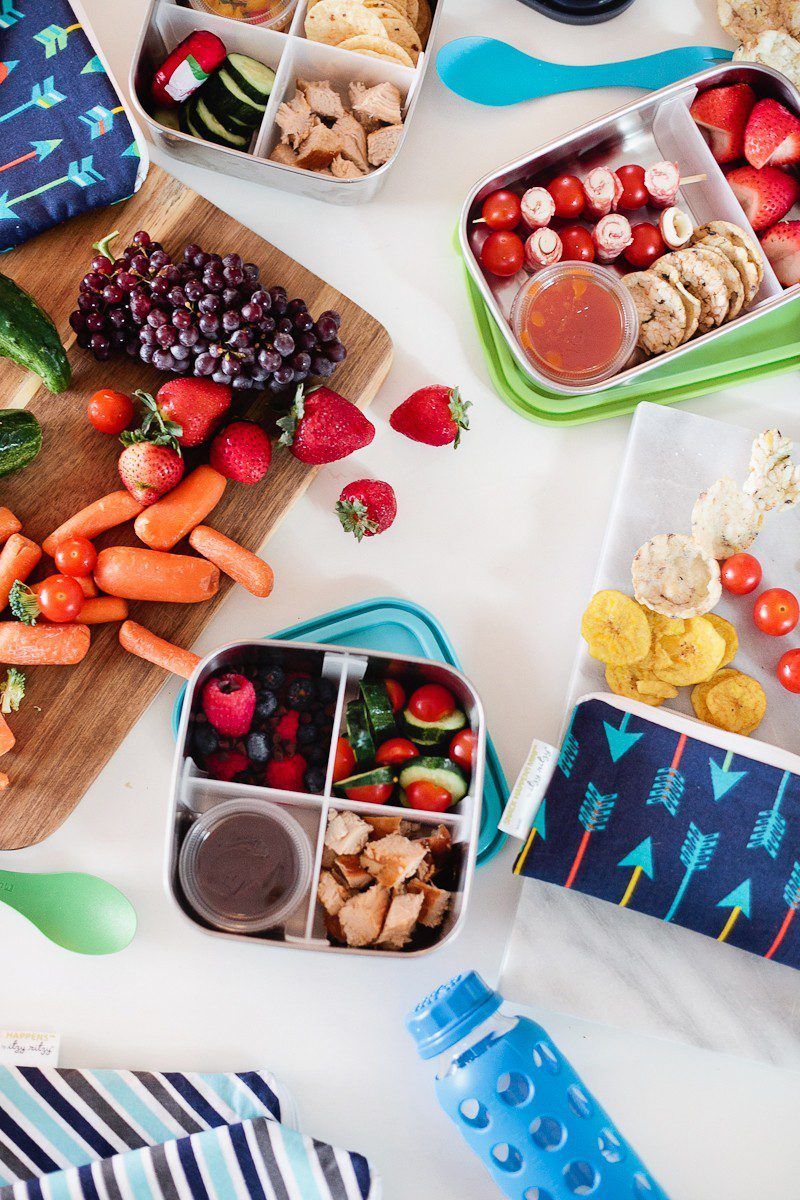 Five lunchbox lunchable hacks that are easy to put together, packed full of nutrients to fuel their school day and can absolutely be made ahead of time so the morning of is still as easy as reaching in the refrigerator. | Healthy Lunchables by popular Florida lifestyle blog, Fresh Mommy Blog: image of various kids lunchables next to some grapes, mini carrots, strawberries, and cherry tomatoes on a wooden cutting board.