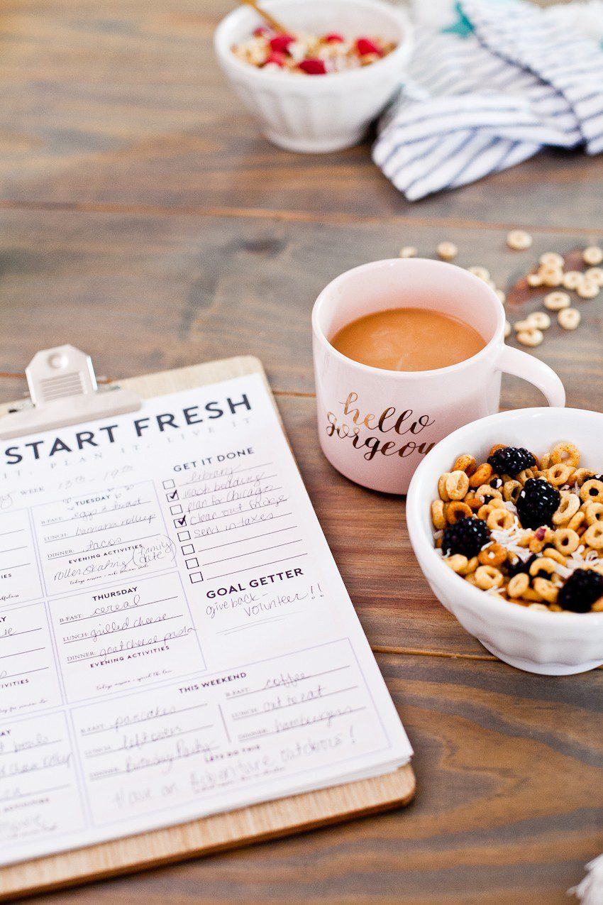 How to Get Ready for School: 5 Sensational Strategies to Make Easy on your Family by popular Tampa life and style blog, Fresh Mommy: image of a bowl of cheerios, a mug of coffee, and a clipboard with a weekly chart on it.