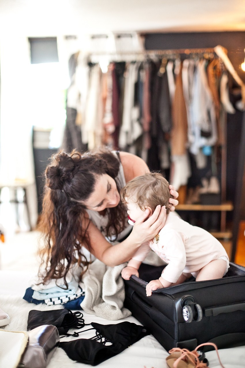Summer travel and beach getaways, how to prepare and pack light. Get that summer glow and get ready to enjoy a beach escape with these tips and tricks!   Beach Vacation by popular Florida travel blog, Fresh Mommy Blog: image of a woman wearing a white tank top and black leggings and packing her black suitcase that her baby is sitting in.