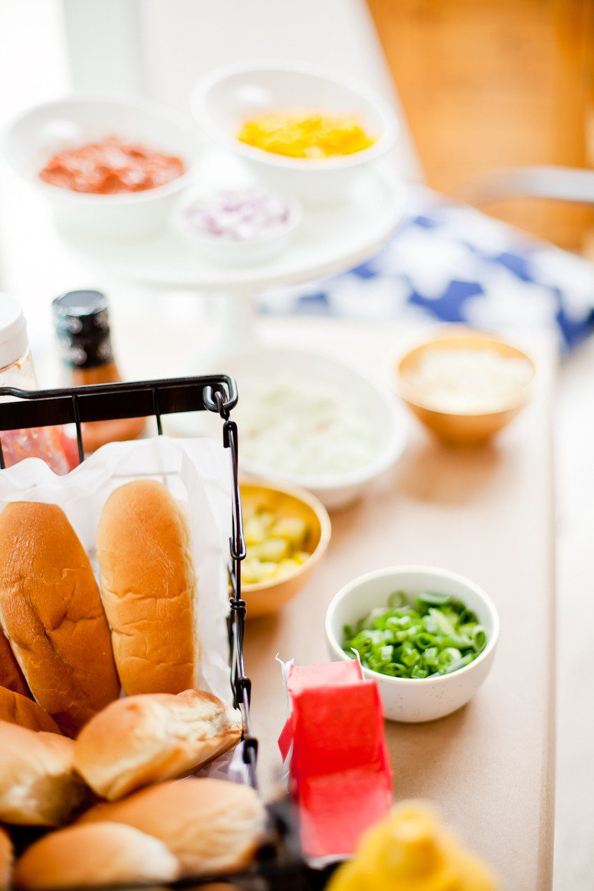Red White and Blue fun, and a DIY Americana Hot Dog Bar! Set up toppings and flavors for all kinds of hot dogs from around the U.S. Chicago style, Boston, Detroit, Philly, Carolina hot dog and more! |  Hot Dog Bar by popular Florida lifestyle blog, Fresh Mommy Blog: image of hot dog buns in a black wire basket.