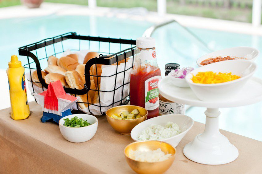 Hot Dog Bar by popular Florida lifestyle blog, Fresh Mommy Blog: image of hot dog buns in a black wire basket next to a ketchup bottle, mustard bottle, and serving bowls filled with green onions, chopped white onions, shredded cheese, and avocado slices.