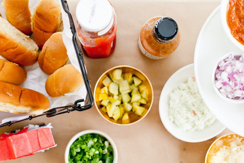 Red White and Blue fun, and a DIY Americana Hot Dog Bar! Set up toppings and flavors for all kinds of hot dogs from around the U.S. Chicago style, Boston, Detroit, Philly, Carolina hot dog and more! |  Hot Dog Bar by popular Florida lifestyle blog, Fresh Mommy Blog: image of hot dog buns in a black wire basket next to a ketchup bottle, diced white onions, diced purple onions, sliced avocados, and green onions.