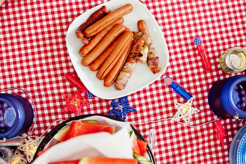 Red White and Blue fun, and a DIY Americana Hot Dog Bar! Set up toppings and flavors for all kinds of hot dogs from around the U.S. Chicago style, Boston, Detroit, Philly, Carolina hot dog and more! |  Hot Dog Bar by popular Florida lifestyle blog, Fresh Mommy Blog: image of a plate of hot dogs on a red and white gingham table cloth next to blue candle votives and a black wire basket filled with watermelon slices.