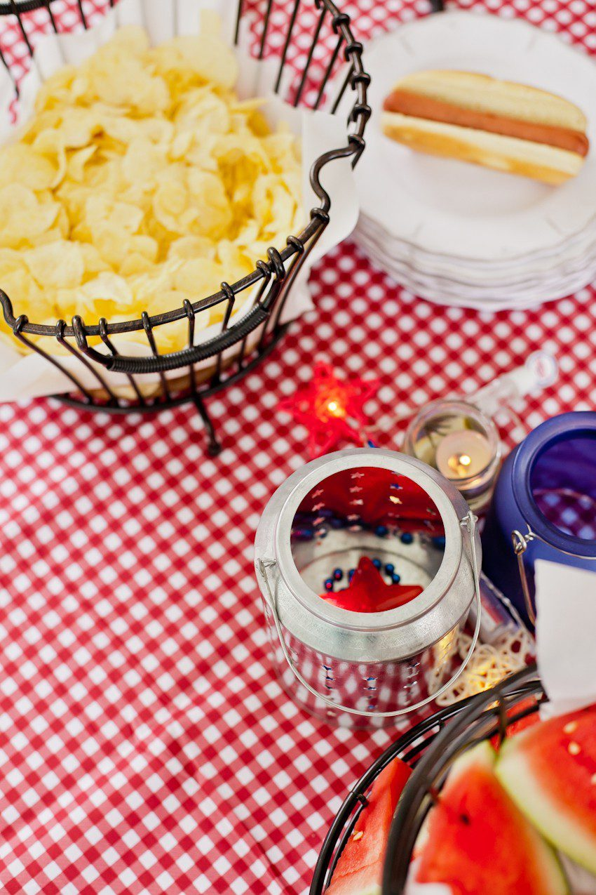 Red White and Blue fun, and a DIY Americana Hot Dog Bar! Set up toppings and flavors for all kinds of hot dogs from around the U.S. Chicago style, Boston, Detroit, Philly, Carolina hot dog and more! |  Hot Dog Bar by popular Florida lifestyle blog, Fresh Mommy Blog: image of a black wire basket filled with potato chips next to a stack of what plates on a red and white gingham table cloth.