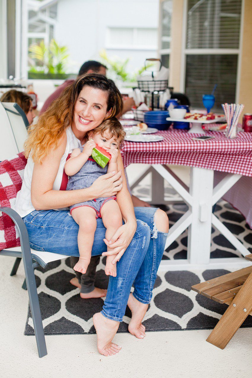 Red White and Blue fun, and a DIY Americana Hot Dog Bar! Set up toppings and flavors for all kinds of hot dogs from around the U.S. Chicago style, Boston, Detroit, Philly, Carolina hot dog and more! |  Hot Dog Bar by popular Florida lifestyle blog, Fresh Mommy Blog: image of a mom sitting outside and holding her baby on her lap as they eat a slice of watermelon.
