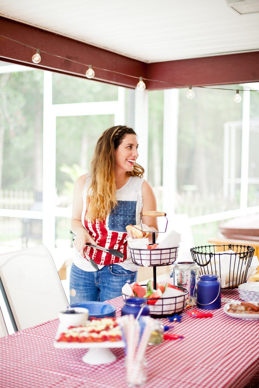 Red White and Blue fun, and a DIY Americana Hot Dog Bar! Set up toppings and flavors for all kinds of hot dogs from around the U.S. Chicago style, Boston, Detroit, Philly, Carolina hot dog and more! | Hot Dog Bar by popular Florida lifestyle blog, Fresh Mommy Blog: image of a woman wearing an American flag tank top and assembling a hot dog at a table with a red and white check table cloth, tiered black wire serving dish with watermelon slices, white serving plate of hot dogs, and American flag fruit platter.