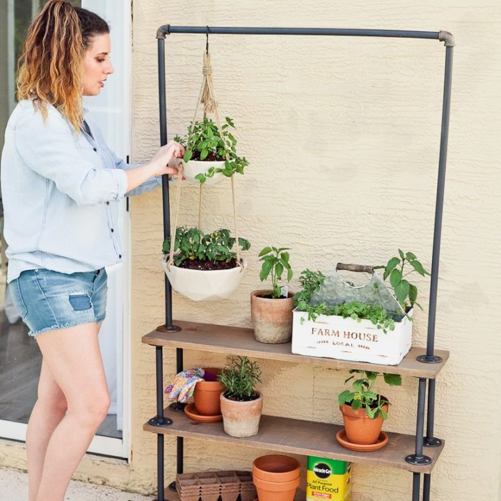 woman watering plants on a DIY rolling plant shelf for portable hanging garden