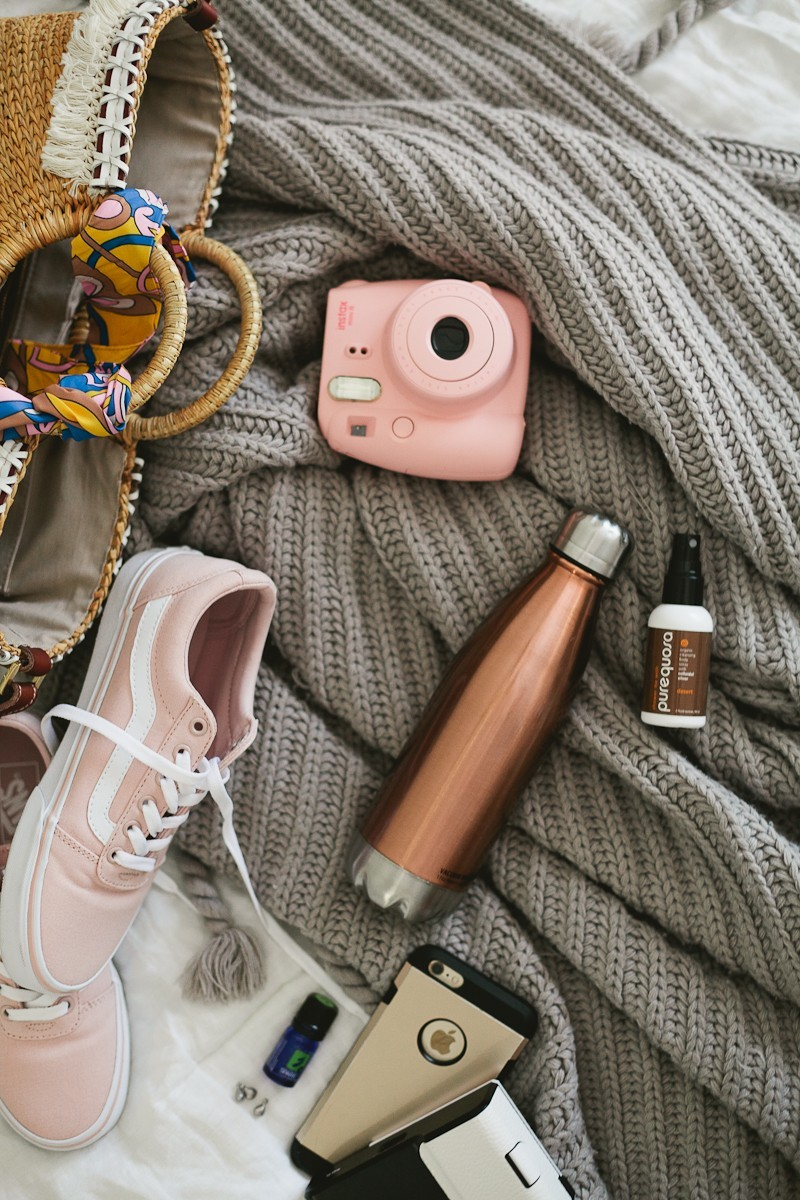 Road Trip Essentials and The Ultimate Road Trip Playlist with music for a happy, adventurous trip. - Travel Essentials: The Ultimate Road Trip Playlist by popular Florida lifestyle blogger Fresh Mommy Blog | Family Road Trip Playlist by popular Florida travel blog, Fresh Mommy Blog: image of a pink Polaroid camera, pink Vans sneakers, inStyle magazine, laptop, water bottle, smartphone and woven handbag.