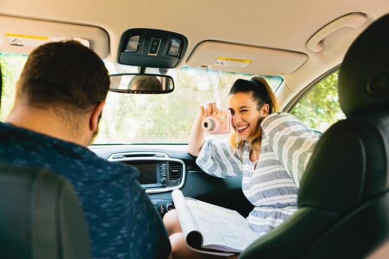 The Ultimate Family Road Trip Playlist: 40+ Songs Everyone Will Love! Make sure your family road trip playlist and journey is JUST AS FUN as the destination with this family road trip playlist and songs that everyone likes to move to. Travel Essentials by popular Florida lifestyle blogger Tabitha Blue of Fresh Mommy Blog | Family Road Trip Playlist by popular Florida travel blog, Fresh Mommy Blog: image of a woman taking a polaroid picture of her husband while they sitting their car.