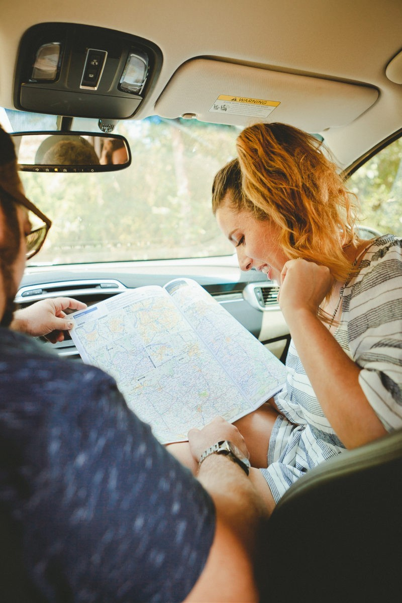 The Ultimate Family Road Trip Playlist with music for a happy, adventurous road trip. - Travel Essentials: The Ultimate Road Trip Playlist by popular Florida lifestyle blogger Fresh Mommy Blog | Family Road Trip Playlist by popular Florida travel blog, Fresh Mommy Blog: image of a woman and her husband looking at a map in their car.