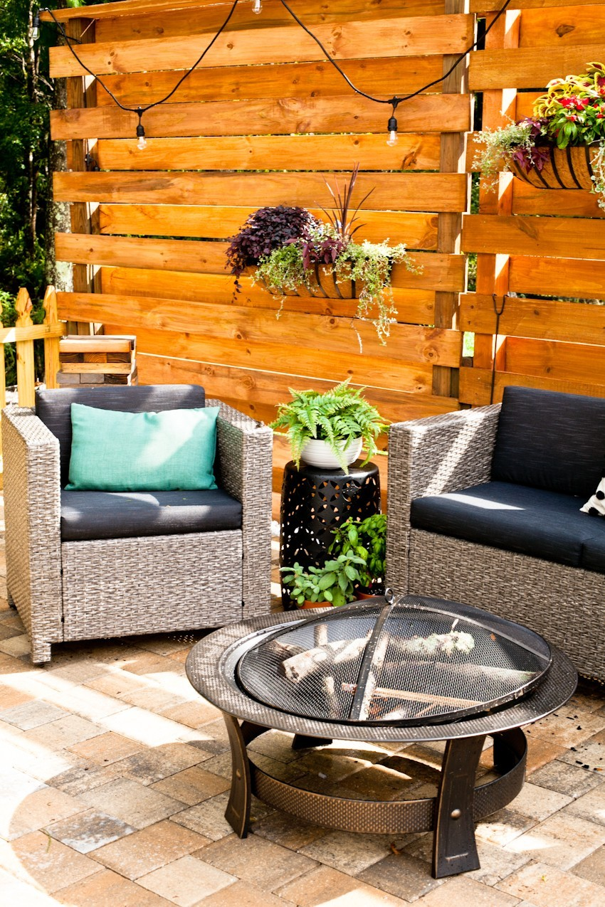 Makeover your backyard space and get ready for grilling season with a slat privacy fence DIY!   Grilling Season by popular Florida lifestyle blog, Fresh Mommy Blog: image of a vertical platen wall, wicker chairs with dark grey cushions and potted plants.