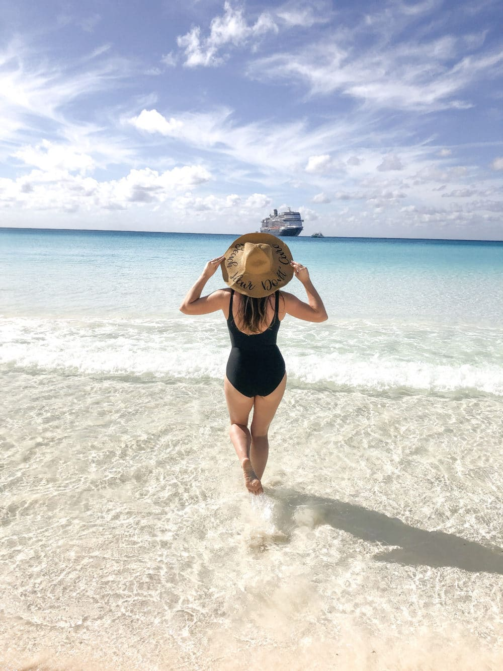 Travel Beauty Essentials featured by top US beauty blog Fresh Mommy Blog; Image of a woman at the beach.