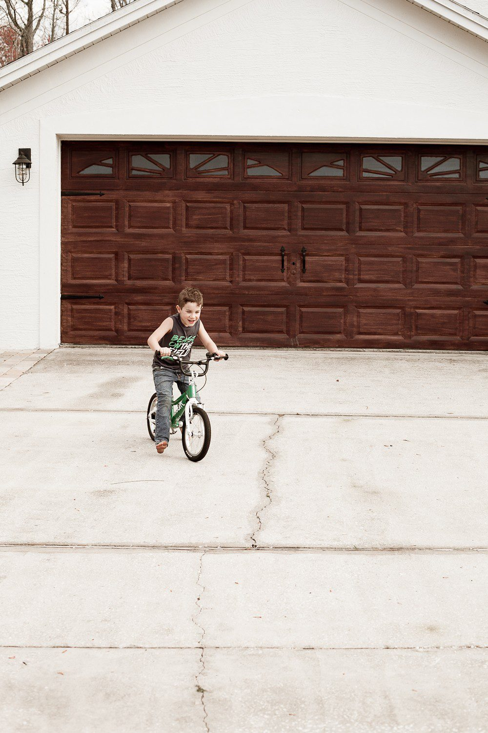 Tips for a DIY Garage Door Makeover and how to Gel Stain a Garage Door to Look Like Wood by popular lifestyle blogger Tabitha Blue of Fresh Mommy Blog: image of young boy riding a bike in front of a white house with a faux wood garage door.