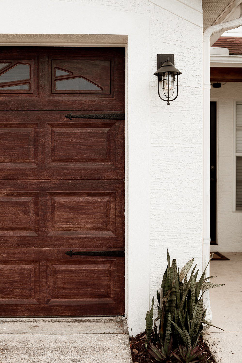 Transform your garage door to a gorgeous faux wood door with this easy gel stain DIY garage door makeover by popular diy blogger Tabitha Blue of Fresh Mommy Blog: image of white house with a faux wood garage door.