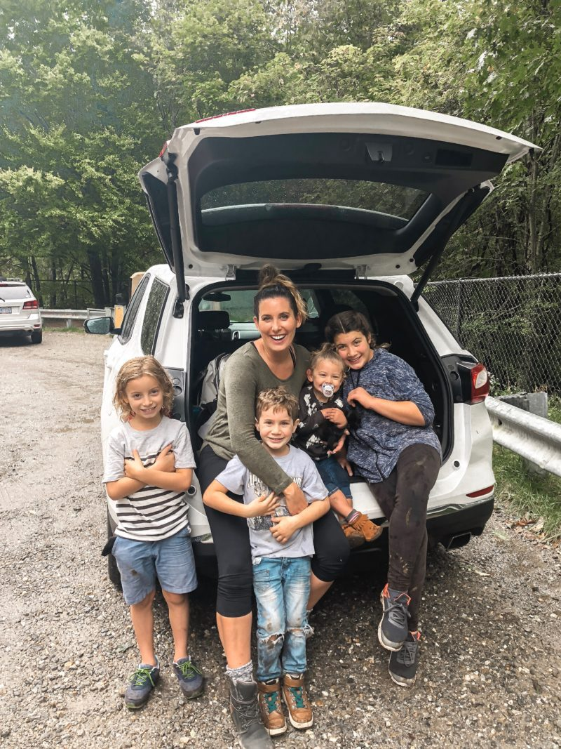 Kitten Care Tips: 5 Essentials you Need to Raise a Cat by popular lifestyel blogger Tabitha Blue of Fresh Mommy Blog: image of mom and 4  young kids sitting in the back of a car and holding a black kitten.