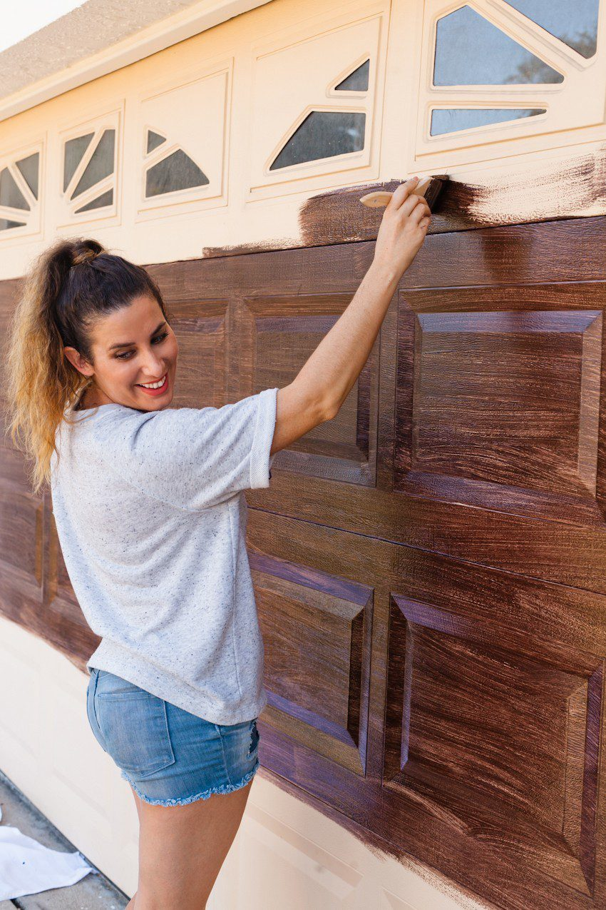 Transform your garage door to a gorgeous faux wood door with this easy gel stain DIY garage door makeover by popular diy blogger Tabitha Blue of Fresh Mommy Blog: image of woman painting a cream garage door to look like faux wood.