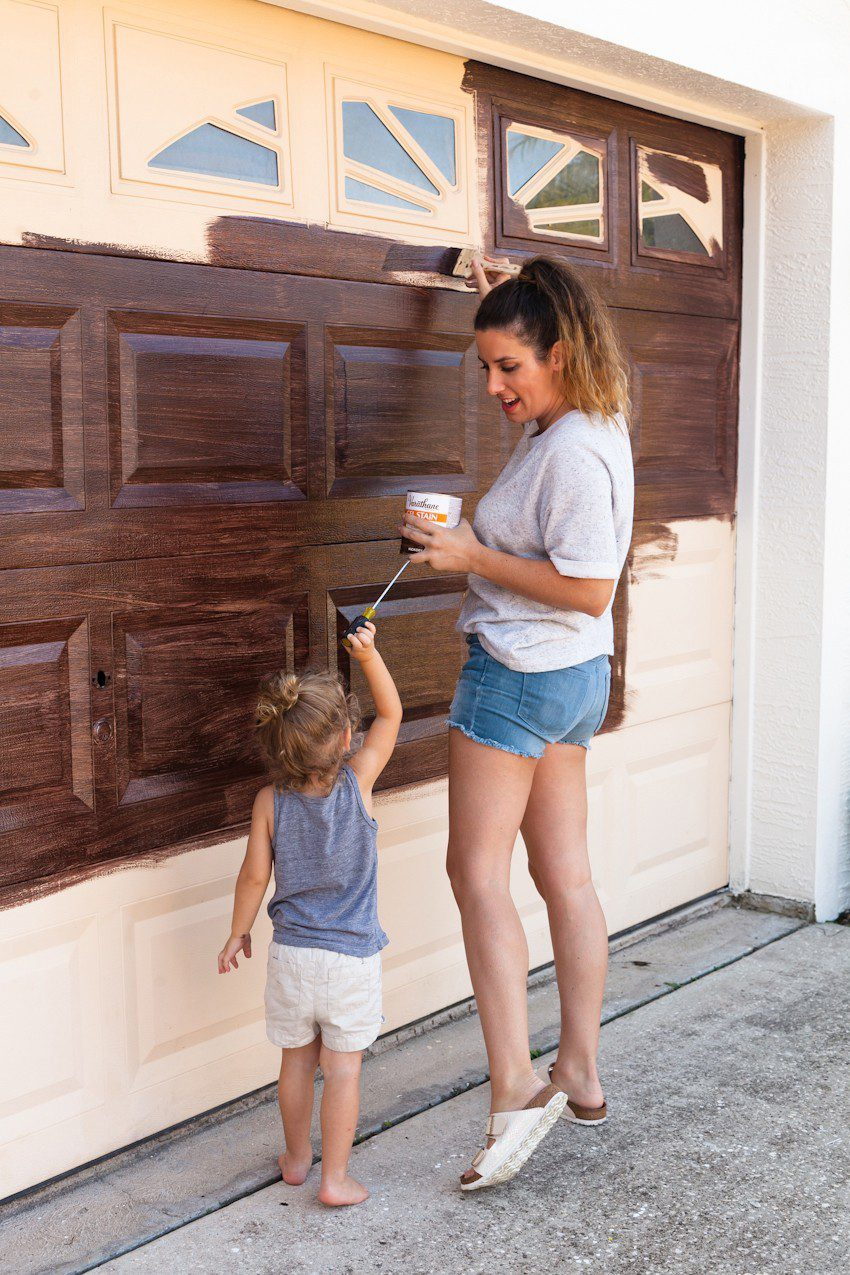 Transform your garage door to a gorgeous faux wood door with this easy gel stain DIY garage door makeover by popular diy blogger Tabitha Blue of Fresh Mommy Blog: image of woman and young girl painting a cream garage door to look like faux wood.