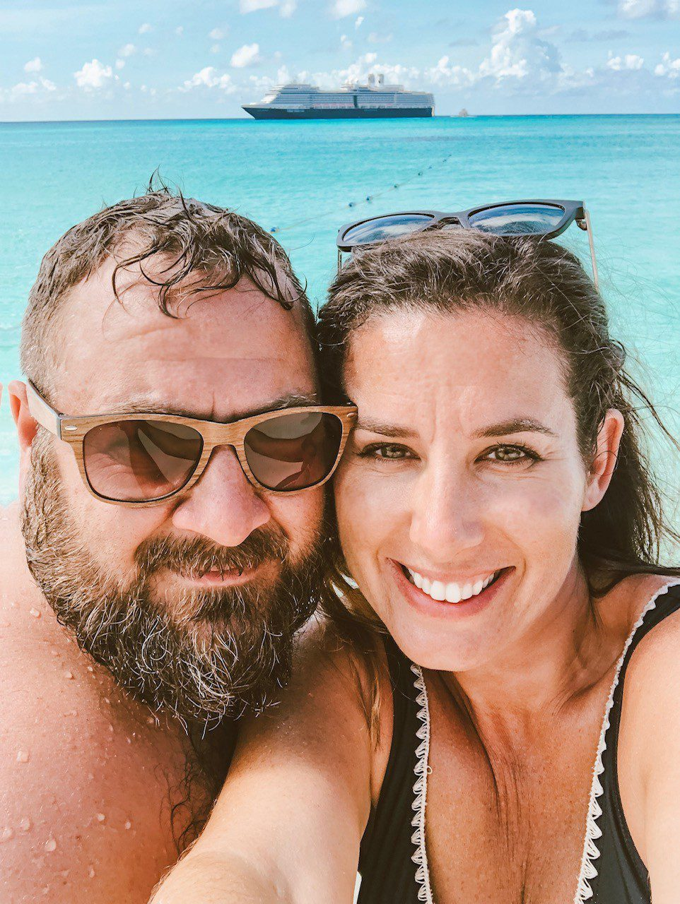 5 Amazing Reason to go on a Holland America cruise with Oprah Magazine by popular US lifestyle blog Fresh Mommy Blog: image of a woman and man standing together in the ocean with a Holland America cruise ship on the horizon.