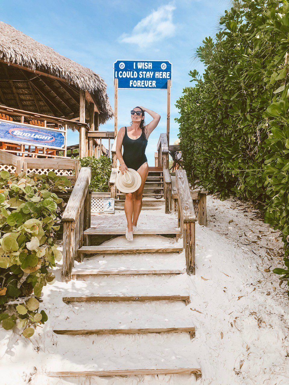 5 Amazing Reason to go on a Holland America cruise with Oprah Magazine by popular US lifestyle blog Fresh Mommy Blog: image of woman wearing a straw sun hat and black swimsuit while standing on a sandy staircase at the beach.