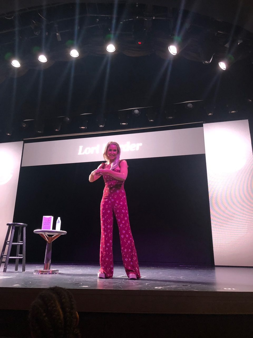 5 Amazing Reason to go on a Holland America cruise with Oprah Magazine by popular US lifestyle blog Fresh Mommy Blog: image of woman in maroon jumpsuit standing on stage and giving a presentation.