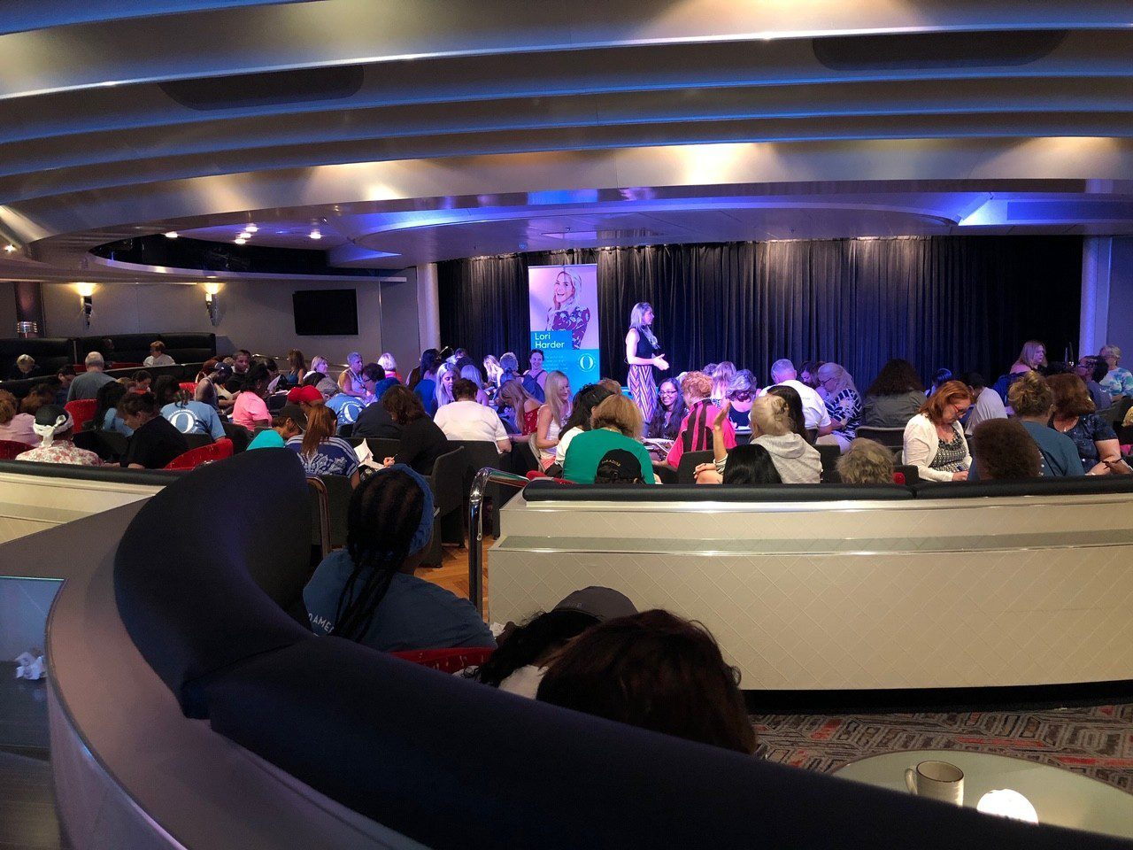 5 Amazing Reason to go on a Holland America cruise with Oprah Magazine by popular US lifestyle blog Fresh Mommy Blog: image of Lori Harder giving a presentation to a group of people on Holland America cruise ship.
