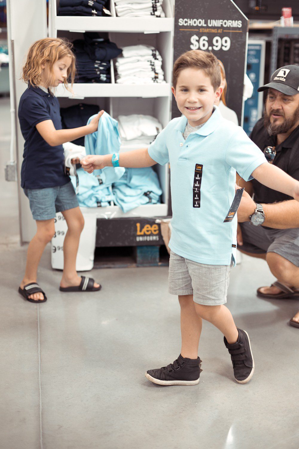5 Sensational Strategies to Make Getting Ready for School Easy | How to Get Ready for School: 5 Sensational Strategies to Make Easy on your Family by popular Tampa life and style blog, Fresh Mommy: image of a dad helping his two young sons try on a blue Lee polo shirt.