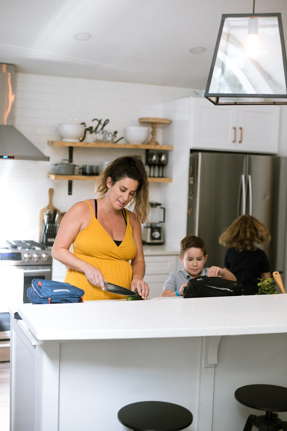 5 Sensational Strategies to Make Getting Ready for School Easy | How to Get Ready for School: 5 Sensational Strategies to Make Easy on your Family by popular Tampa life and style blog, Fresh Mommy: image of a woman standing her kitchen cutting a cucumber while her kids pack things into their lunch bags.
