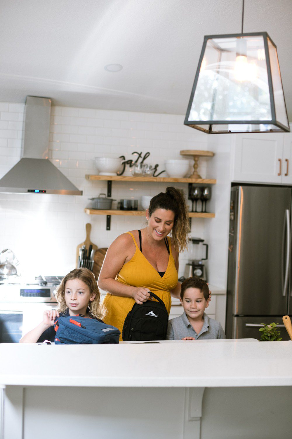 5 Sensational Strategies to Make Getting Ready for School Easy | How to Get Ready for School: 5 Sensational Strategies to Make Easy on your Family by popular Tampa life and style blog, Fresh Mommy: image of a woman standing her kitchen and helping her kids pack their lunch boxes.
