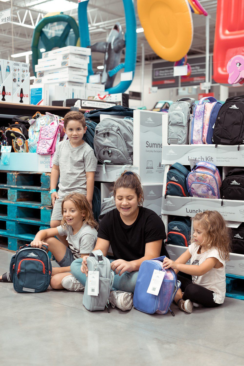 5 Sensational Strategies to Make Getting Ready for School Easy | How to Get Ready for School: 5 Sensational Strategies to Make Easy on your Family by popular Tampa life and style blog, Fresh Mommy: image of 4 young kids sitting in front of a backpack and lunch box display.