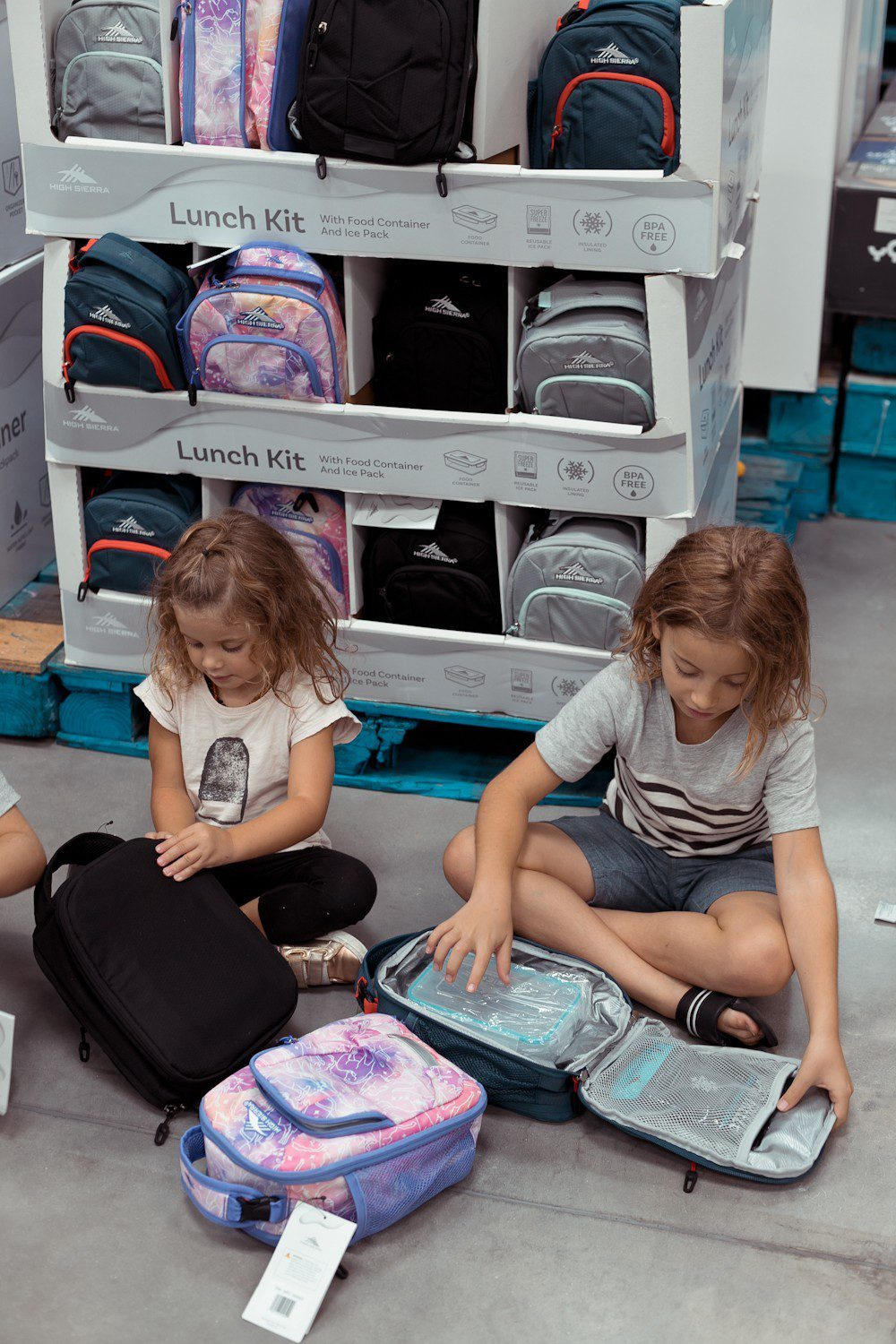 5 Sensational Strategies to Make Getting Ready for School Easy | How to Get Ready for School: 5 Sensational Strategies to Make Easy on your Family by popular Tampa life and style blog, Fresh Mommy: image of 2 young kids sitting in front of a backpack and lunch box display.