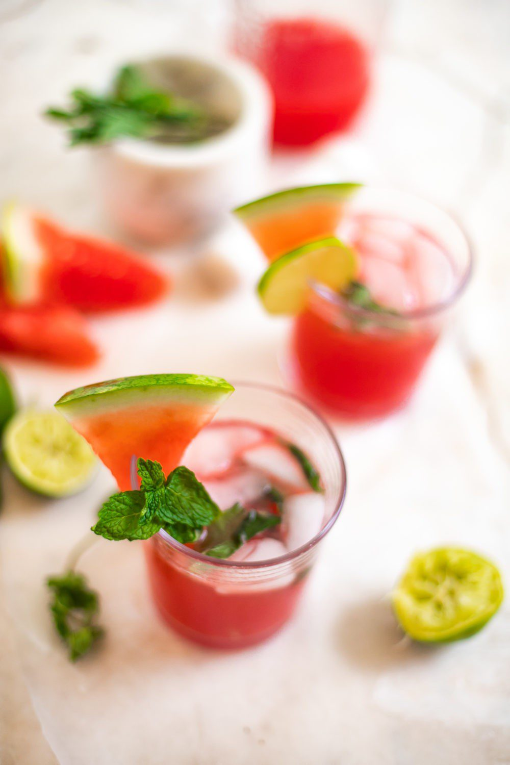 Refreshingly Easy Summer Mocktail Recipes! by popular Florida lifestyle blog, Fresh Mommy: image of Watermelon mojiotos on a marble countertop surrounded by lime halves and watermelon slices.