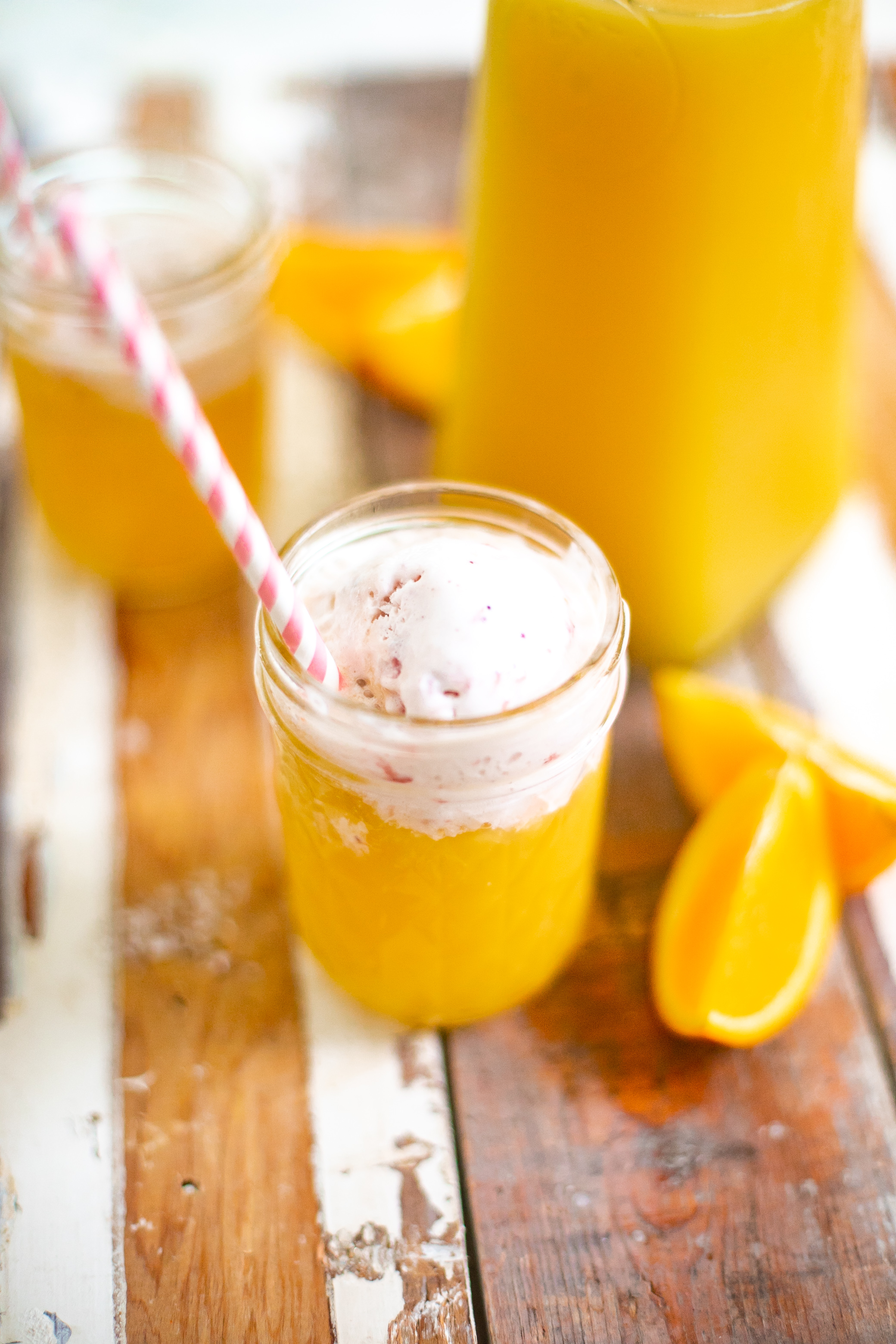 Refreshingly Easy Summer Mocktail Recipes! by popular Florida lifestyle blog, Fresh Mommy: image of a orange Summer Sorbet mocktail in mason jars with a pink and white striped straws resting a distressed wood plank counter top next to some orange slices.