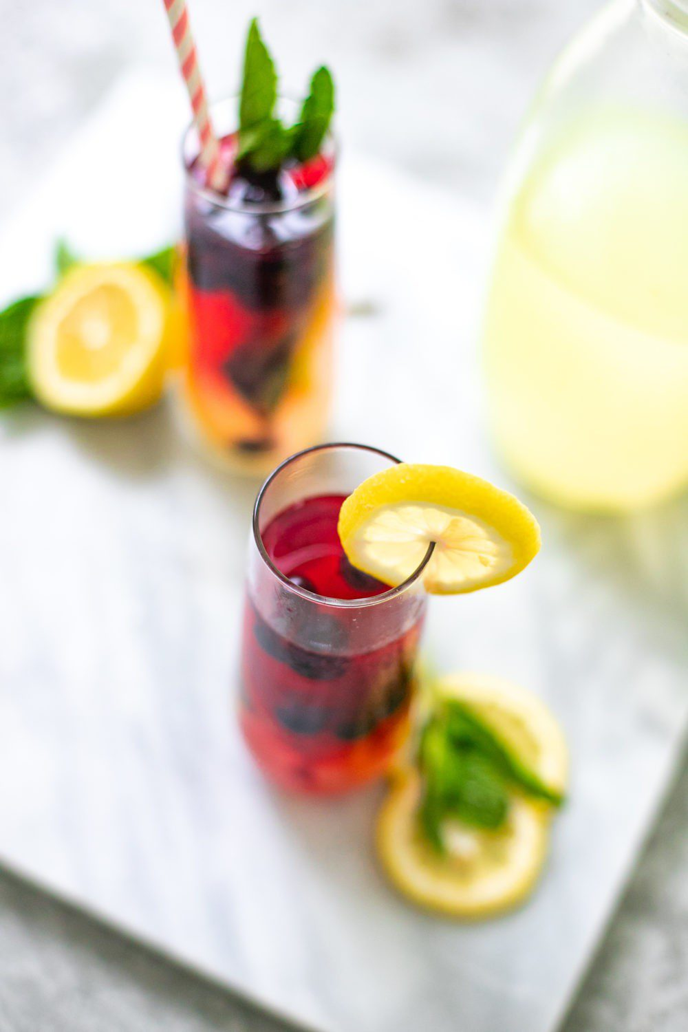Refreshingly Easy Summer Mocktail Recipes! by popular Florida lifestyle blog, Fresh Mommy: image of Minty Blueberry Lemonade Summer Mocktail Spritzer with a pink and white stripe straw and a lemon slice on the rim of the cup and some fresh mint leaves in the top of the drink.