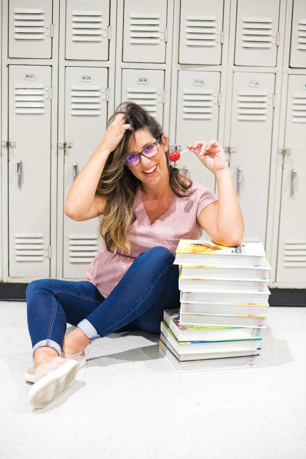 Back to School Eye Exam: How to Prepare your Child for a Successful Academic Year | Back to School Eye Exam: How to Prepare your Child for a Successful Academic Year by popular Florida lifestyle blog, Fresh Mommy Blog: image of a woman sitting in front of some school lockers wearing a pair of blue light glasses, holding a sucker, and resting her elbow on a stack of books.