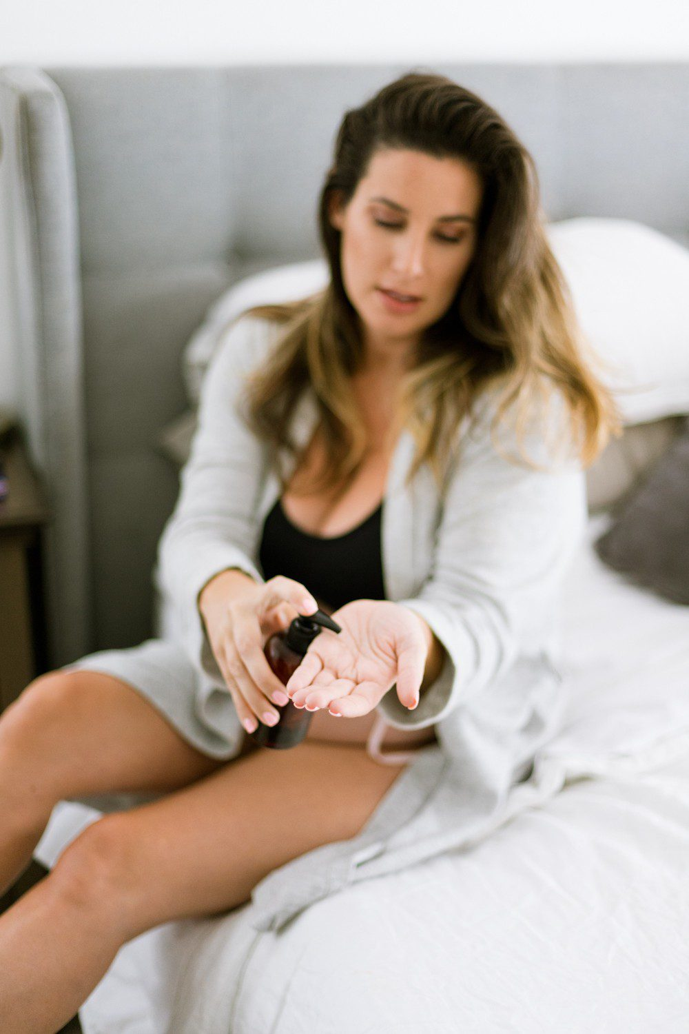 Top 10 Essential Oils While Pregnant That are Completely Safe by popular Florida lifestyle blog, Fresh Mommy: image of woman sitting on her bed in a grey robe, black sports bra, and black underwear and applying some essential oils to her hand from a brown glass dispenser.