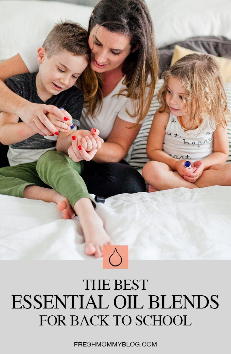 The Best Smelling and Most Effective Essential Oil Blends for Back to School! From helping with focus, to curbing lice and germs, we're sharing all the ways to use essential oils for back to school. From Popular Florida Lifestyle blogger Tabitha Blue of Fresh Mommy Blog. | Best Smelling Back to School Essential Oils by popular Florida life and style blog, Fresh Mommy: Pinterest image of a mom sitting in bed with her two kids and help them apply essentials oils to their wrists.