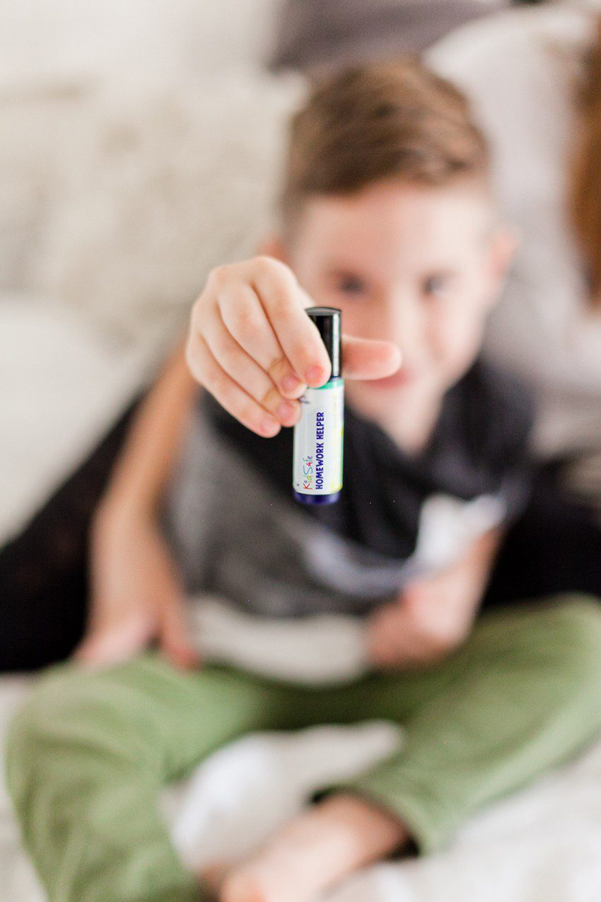 The Best Smelling and Most Effective Essential Oil Blends for Back to School! From helping with focus, to curbing lice and germs, we're sharing all the ways to use essential oils for back to school. From Popular Florida Lifestyle blogger Tabitha Blue of Fresh Mommy Blog. | Best Smelling Back to School Essential Oils by popular Florida life and style blog, Fresh Mommy: image of a young boy holding out a bottle of kid safe homework helper essential oils.