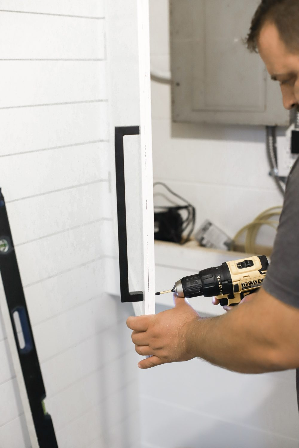 DIY for Covering Breaker Boxes: A Faux Cabinet Tutorial by popular Florida DIY blog, Fresh Mommy: image of a man screwing some handles on to some cabinets.