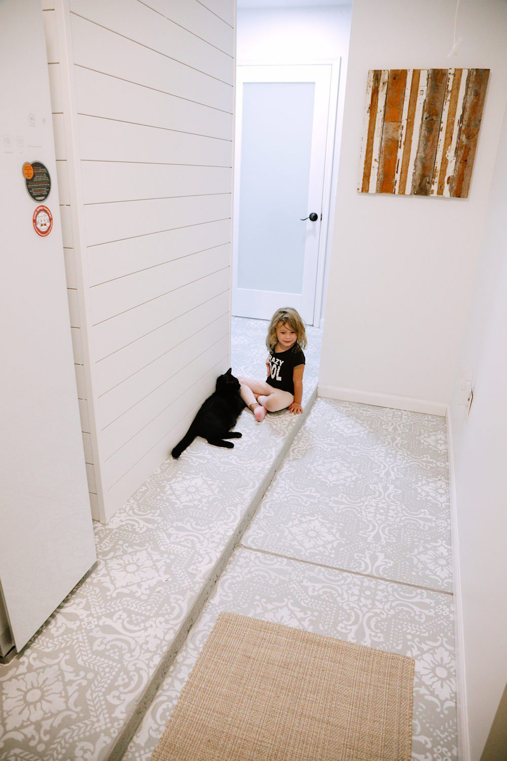How We Designed a Family Friendly Laundry Room in our Garage - The Reveal! Stenciled floors, DIY covers for breaker boxes and utilities, large capacity appliances, organization tips and more! | Laundry Room DIY: How to Paint a Cement Floor with Stencils by popular home decor blog, Fresh Mommy: image of a laundry room with a painted cement floor.