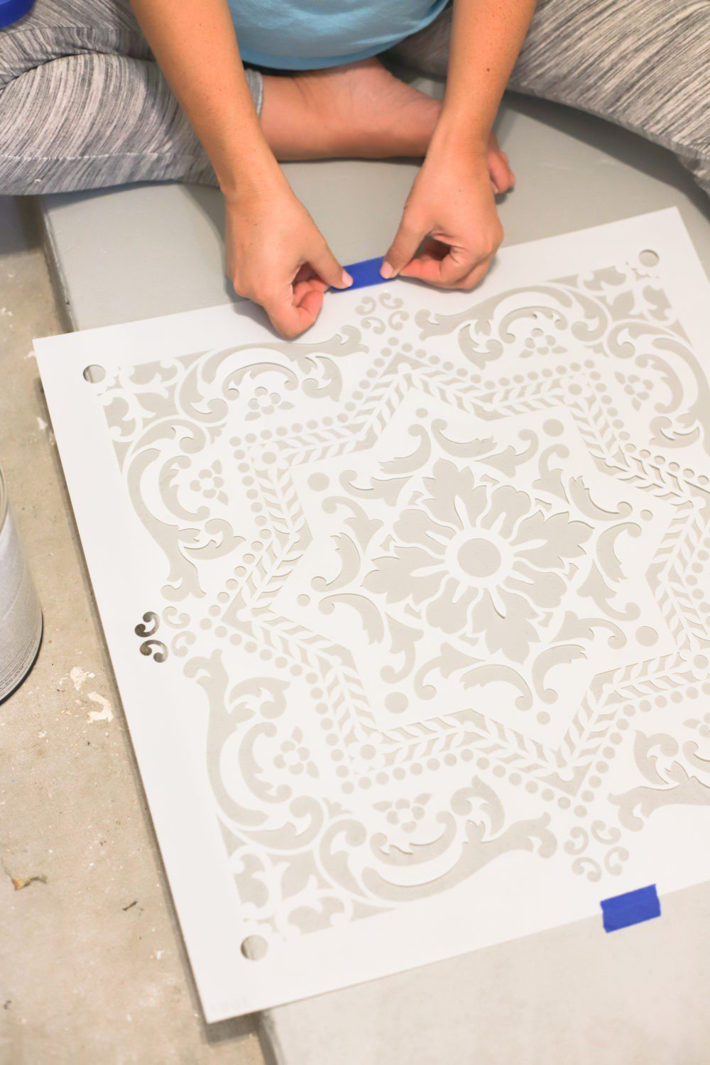 Laundry Room DIY: How to Paint a Cement Floor with Stencils | Laundry Room DIY: How to Paint a Cement Floor with Stencils by popular home decor blog, Fresh Mommy: image of a floor stencil being taped down.