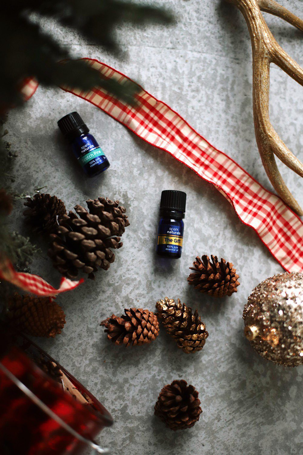 Hopefully, you are enjoying all the love, happiness, and high spirits the holidays bring, though research shows that approximately 70% of people experience stress during the holidays due to time and money pressures. When you are having those conflicting feelings it is important to focus on the positive. One thing that truly helps reduce stress and fill our home with joy is through using Christmas Essential Oils. It might sound crazy, but one of the known benefits of essential oils is that they can lift your mood. There are numerous other benefits of essential oils, so we compiled a list of the top Christmas essential oils that can help you through the holiday season with a smile on your face. We're breaking them all down below for 12 days of Christmas essential oils!   12 Christmas Essential Oils to Fight Stress by popular Florida life and style blog, Fresh Mommy: image of Spark Naturals The Gift and Scotch Pine essential oils.