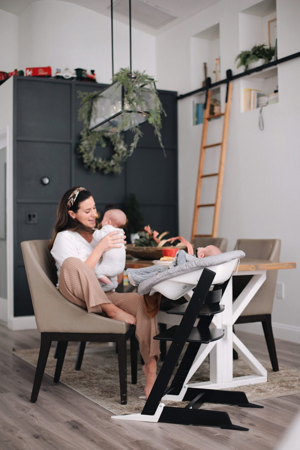 A DIY Grid Wood feature wall in black! | Gorgeous Wood Feature Wall + Shared Girl's Room Update by popular Florida home decor blog, Fresh Mommy Blog: image of a woman sitting at a dining table and holding her twin babies.