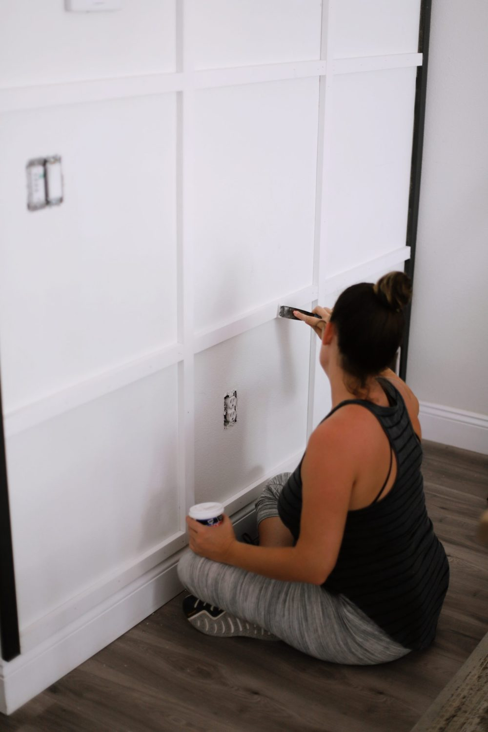 BEFORE AND AFTER Tutorial: DIY Wood Grid Wall! How to create a stunning and bold accent wall with a DIY wooden grid. Click for the full tutorial. | Tutorial: Board and Batten Grid Wall by popular Florida DIY blog, Fresh Mommy Blog: image of a woman painting some trim on her board and batten grid wall.
