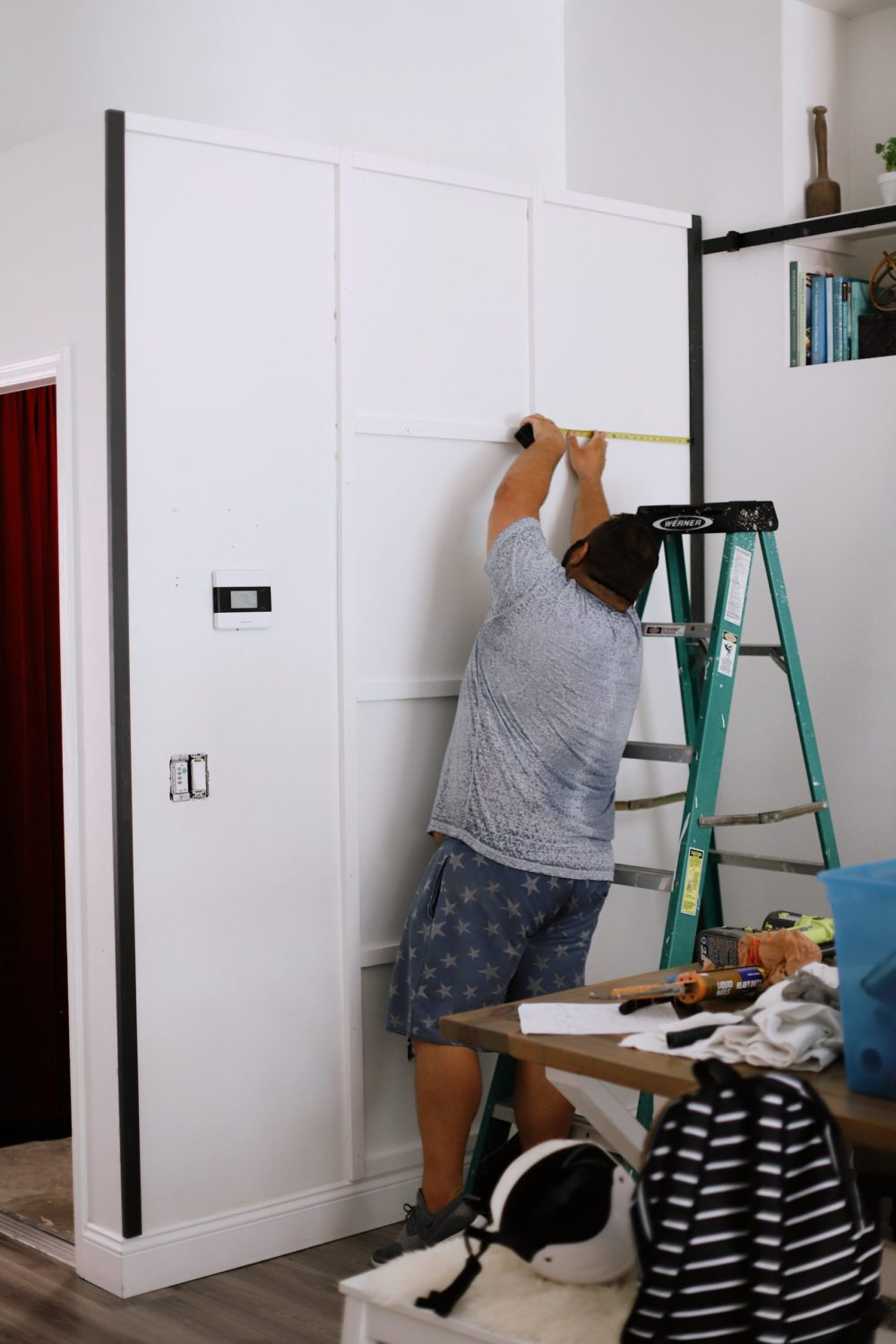 BEFORE AND AFTER Tutorial: DIY Wood Grid Wall! How to create a stunning and bold accent wall with a DIY wooden grid. Click for the full tutorial. | Tutorial: Board and Batten Grid Wall by popular Florida DIY blog, Fresh Mommy Blog: image of a man measuring a wall.