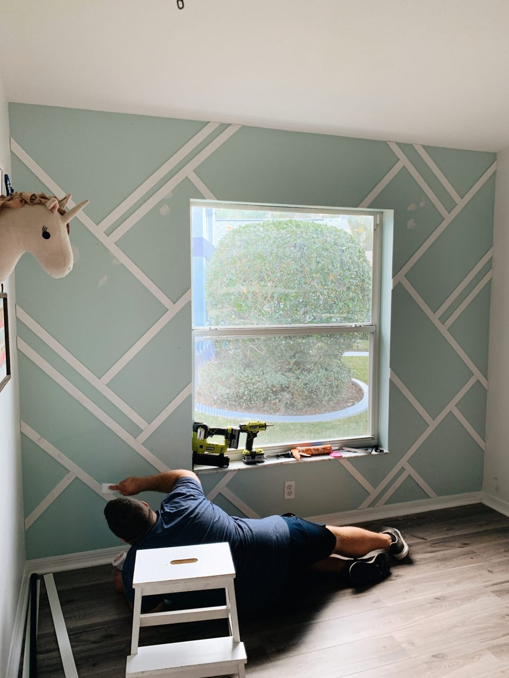 How to DIY a wood design accent wall | Gorgeous Wood Feature Wall + Shared Girl's Room Update by popular Florida home decor blog, Fresh Mommy Blog: before image of a man installing a wood accent wall in a shared girls' room.
